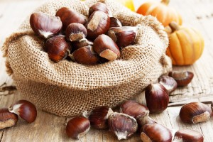 Bag with Chestnuts on Wooden Table,edible autumn fruits